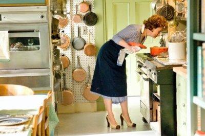 Em sua cozinha decorada à caráter, a personagem Julia Child sente o aroma do que prepara
