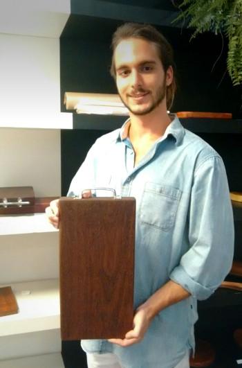 O artesão e dono da Taubá, Theo Guarnieri, e uma de suas tábuas com alças de aço inox